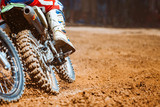 Fototapety Close-up part of mountain bikes race in dirt track with flying debris during an acceleration in sunshine day time. Concept of focus between an accelerate in action sport
