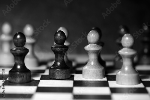 Plakat Chess figures on a chessboard. Black and white