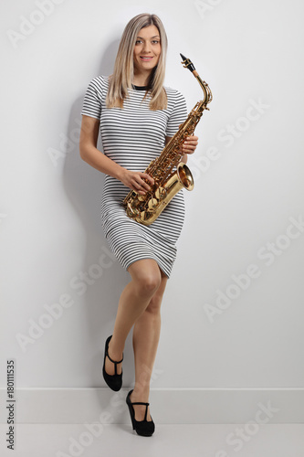 Fotobehang Muziek Full length portrait of a young woman holding a saxophone