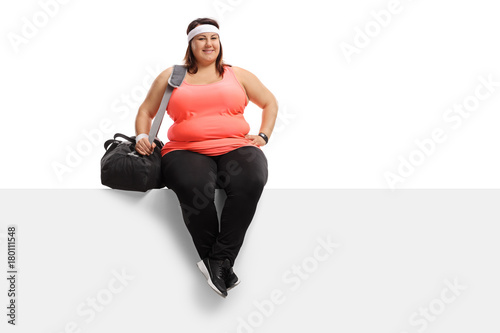 Overweight woman with a sports bag sitting on a panel