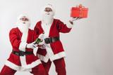 babbo natale apre una bottiglia di spumante mentre l'altro mostra un regalo con pacco rosso - sfondo chiaro - 180113790