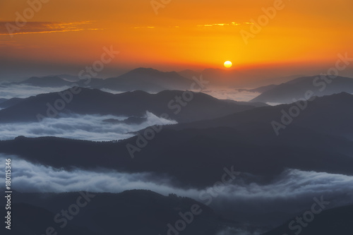 sunrise on distant mountains with morning fog