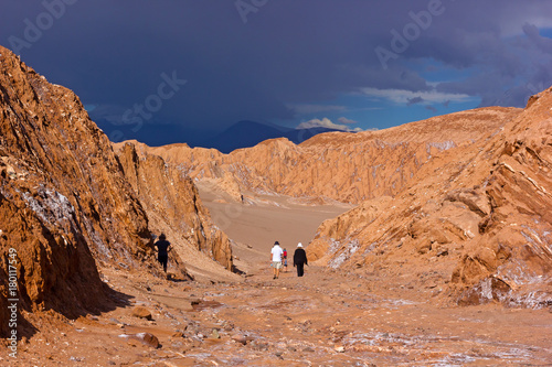 Fotobehang Zalm Approaching thunder in Atacama Desert, Chile. Tourists explore rock formations and sandy hills on the deserted landscape.