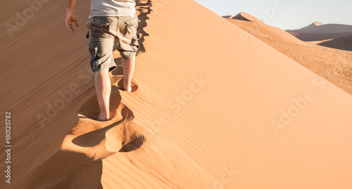 Lonely man walking on sand crest at Dune 45 in Sossusvlei desert - Wanderlust concept with hiker guy in namibian famous place - Adventure trip travel to african wonder in Namibia - Bright natural tone