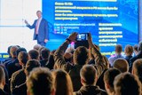 Man takes a picture of the presentation at the conference hall using smartphone - 180137129