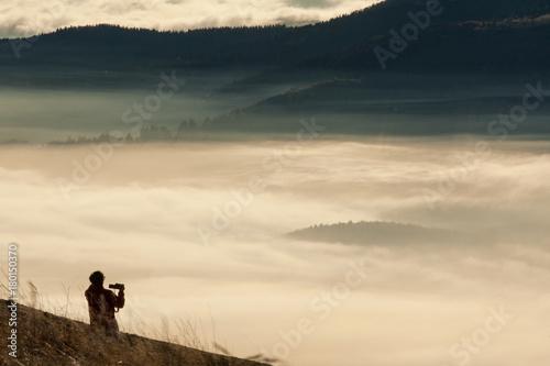 Frau, die den Sonnenaufgang fotografiert Poster
