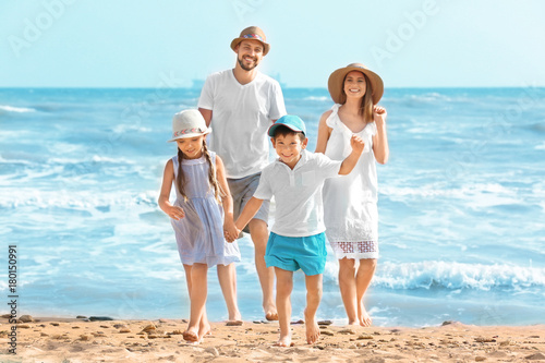 Happy family on sea beach at resort - 180150991