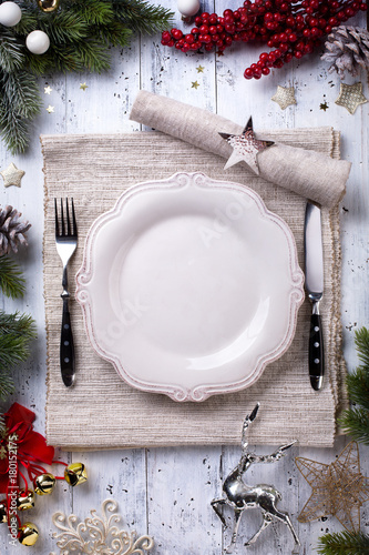 Christmas holiday dinner background; empty dish, cutlery and Christmas tree decoration - 180152175
