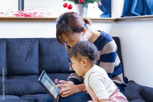 窓辺のソファでタブレットのコンテンツを楽しむ母親と1歳の女の子