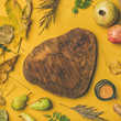 Autumn morning coffee concept. Flat-lay of cup of espresso and wooden board in center over mustard yellow background with dried fallen leaves and fruits around, top view, copy space, square crop