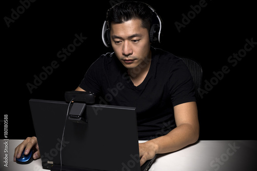 Competitive asian male professional E Sports video gamer playing an FPS, or MMO game on a computer and streaming online Poster