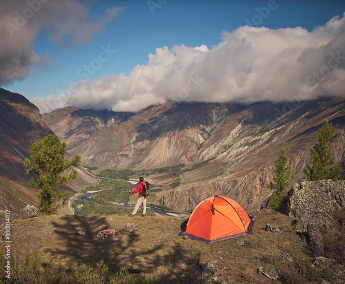 Papiers peints Cappuccino Person stands near the camping and look at the mountain valley