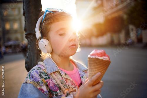 Fotobehang Muziek little girl listening music on street and eating ice cream