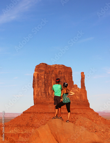 Tuinposter Baksteen Couple Hiking Monument Valley with one of The Mittens