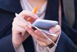 メモを取りながらスマートフォンを使う女性 - 180197588
