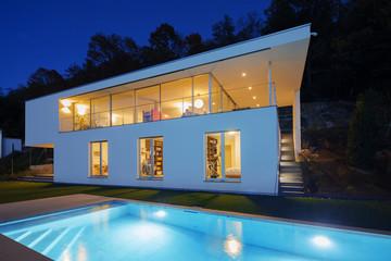 Modern villa, exterior in the night, lights on