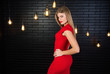 Beautiful attractive girl in a red dress on a background of black wall with lights bulbs