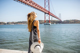 Woman enjoying beautiful landscape view on the famous iron bridge standing back near the river in Lisbon, Portugal - 180220367