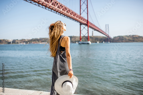 mata magnetyczna Woman enjoying beautiful landscape view on the famous iron bridge standing back near the river in Lisbon, Portugal