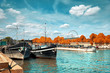 Seine riverbank in Paris with historical boats moored by the shore and passenger ship