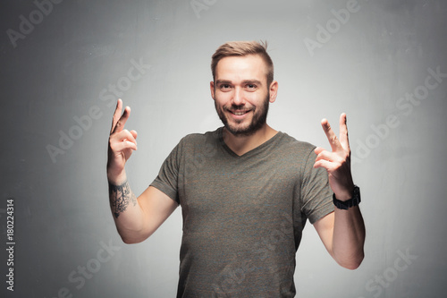 Young man showing peace sign.