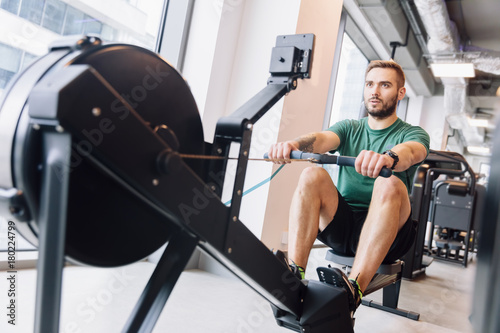 Poster Active athlete man doing rowing workout