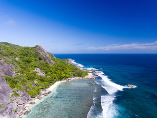 Aerial view of coral reef with mountains, rocks and vegetation