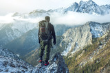 Man hiker with backpack on top of the mountain back, looking at the snow slope. Concept motivation and goal achievement - 180227584