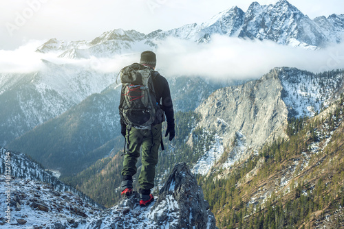 Fototapeta Man hiker with backpack on top of the mountain back, looking at the snow slope. Concept motivation and goal achievement