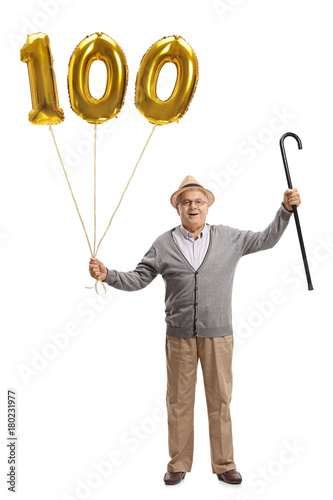 Happy senior with a golden number hundred balloon and a cane