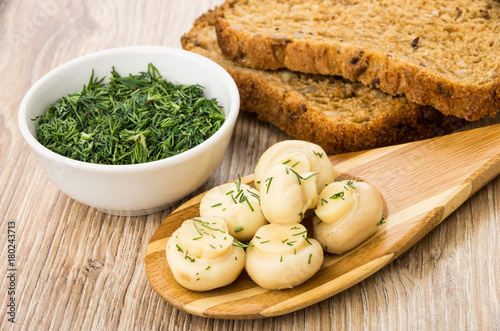 Fototapeta Marinated champignons with dill on bamboo spoon, dill in bowl