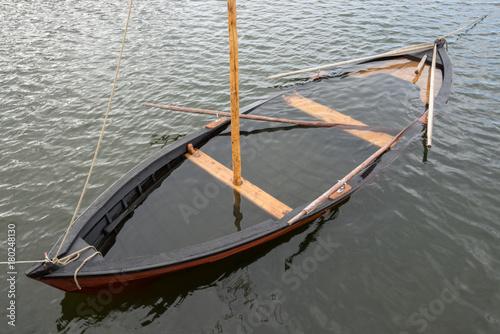 Aluminium Schipbreuk Wooden sailboat on the sea, water inside. Boat under water.