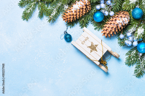 Christmas background on blue table. Top view. Christmas fir tree, blue balls, sled and pine cones.