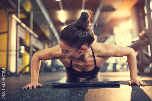 Wall mural Woman in gym putting arms in proper position for pushups exercise