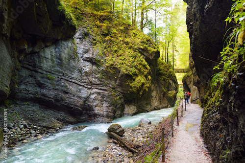 Blue water flowing in the Partnach Gorge or Partnachklamm, incised by a mountain stream in the Reintal valley near the town of Garmisch-Partenkirchen. - 180285194