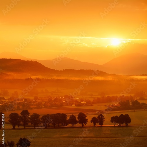 Deurstickers Baksteen Breathtaking morning lansdcape of small bavarian village covered in fog. Scenic view of Bavarian Alps at sunrise with majestic mountains in the background.