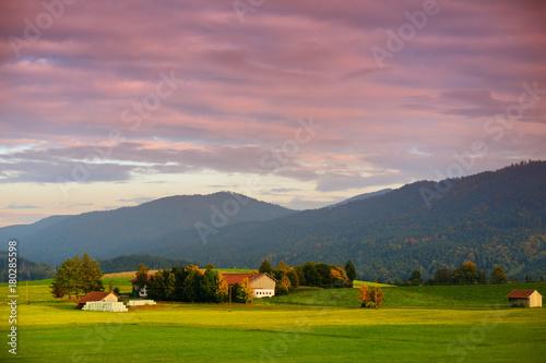 Foto op Plexiglas Ochtendgloren Breathtaking lansdcape of Austrian countryside on sunset. Dramatic sky over idyllic green fields of Anstrian Central Alps on autumn evening.
