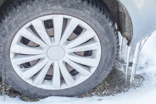 Foto op Aluminium Bergen Huge icicles on the dirty car wheel. Dangerous Frozen ice build up wheel fender arch. Driving problems. Extreme winter snow series. Close up tire on the snowy road.