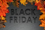 Black Friday text with autumn leaves on black slate background - 180293113