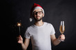 Merry Christmas and Happy New Year. People, leisure and vacations. Portrait of attractive young man with happy joyful smile dressed in red hat with white fur taking bengal light and glass of champagne