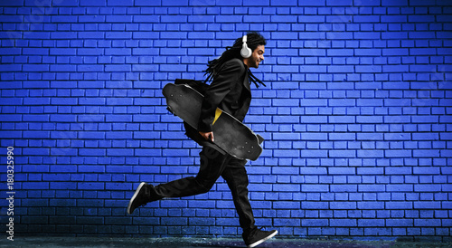 Fotobehang Skateboard Stylish young dreadlocks hipster with headphones walking with a skate in hand near the blue brick wall on the street.