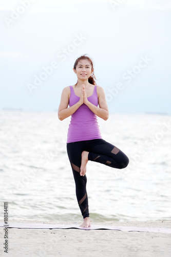 Fotobehang School de yoga Young healthy asian woman practicing yoga standing in tree pose asana on sea beach background, people sport and healthy lifestyles, wellness, well being concept