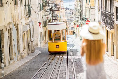 mloda-kobieta-turysta-fotografuje-slawnego-retro-zoltego-tramwaju-na-ulicie-w-lisbon-miescie-portugalia-kobieta-jest-nieostra