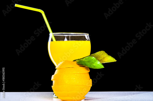 Fotobehang Sap glass with orange juice, a cut orange on a black background