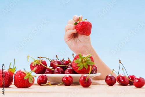 Aluminium Kersen Top of wood table, hand with cherry on sky background