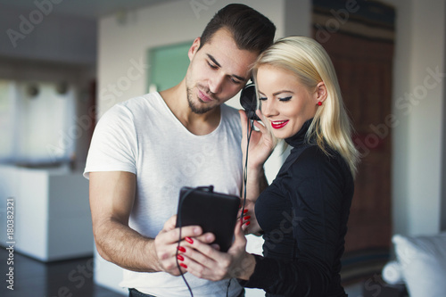 Fotobehang Muziek Young couple listening music by tablet at home