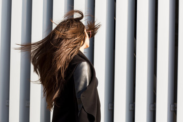 Brunette woman with shiny lush hair blowing in wind, walking at the street