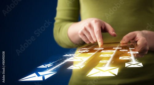 Hand holding tablet and sending email icons