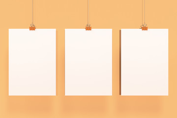 Three blank white posters with binder clip mockup on orange background