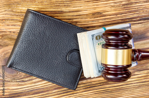 Judges hammer with folded dollars and wallet on the table. Top view.